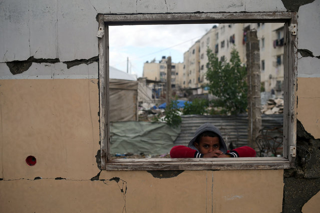 A Palestinian boy looks on from the window of a building that was destroyed during the 50-day war between Israel and Hamas-led militants in January 2015, during a winter storm in Beit Hanoun in the northern Gaza Strip on January 25, 2016. (Photo by Mohammed Abed/AFP Photo)