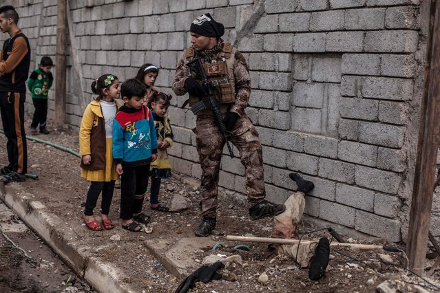 In this Sunday, December 18, 2016 photo, Iraqi children look at the body of a half-buried Islamic State militant while talking to an Iraqi soldier in the al-Barid district in Mosul, Iraq. In a part of Mosul that had been reclaimed from the Islamic State group (IS) days ago, Iraqi special forces were attacked on Sunday by drones operated by IS fighters inside the city. (Photo by Manu Brabo/AP Photo)