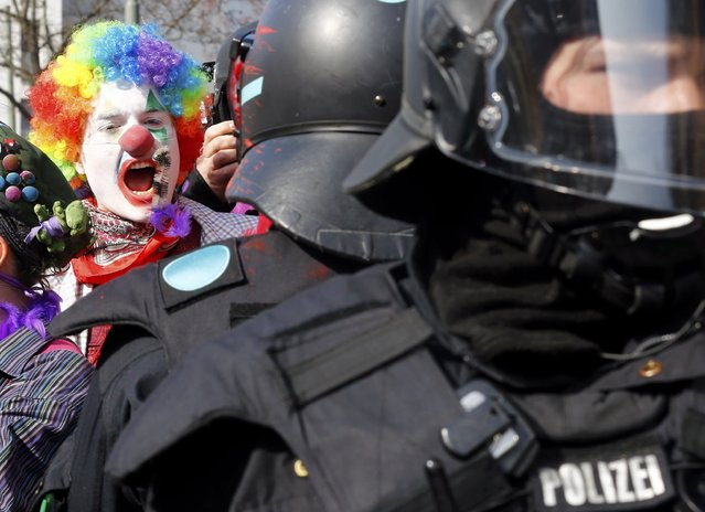 An anti-capitalist protester dressed as a clown shouts behind policemen near the European Central Bank (ECB) building before the official opening of its new headquarters in Frankfurt March 18, 2015. (Photo by Michael Dalder/Reuters)