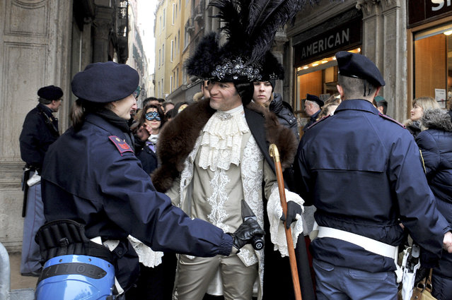 A Police officer checks a man wearing a carnival costume in Venice, Italy, Sunday, January 31, 2016. Carnival-goers in Venice are being asked by police to momentarily lift their masks as part of new anti-terrorism measures for the annual festivities. Police are also examining backpacks and bags and using metal-detecting wands before revelers are allowed into St. Mark's Square, the heart of the Venetian carnival. (Photo by Luigi Costantini/AP Photo)
