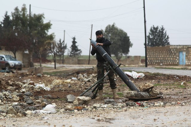 A Free Syrian Army fighter places a shell before firing it towards Islamic State fighters in the northern Aleppo countryside, Syria, January 18, 2016. (Photo by Abdelrahmin Ismail/Reuters)
