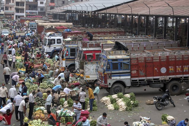Indians crowd a vegetable market in Jammu, India, Tuesday, May 4, 2021. COVID-19 infections and deaths are mounting with alarming speed in India with no end in sight to the crisis. (Photo by Channi Anand/AP Photo)