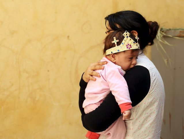 An Egyptian Coptic Christian carries her baby who wears a palm decoration during Palm Sunday inside a church in Old Cairo, April 5, 2015. (Photo by Asmaa Waguih/Reuters)