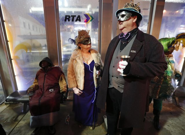 """Chuck Rogers, left, and Kathleen Barrow, inaugural King and Queen of the """"Societe des Champs Elysee"""" disembark the Rampart-St. Claude street car line next to a man sitting at a street car stop, to commemorate the official start of Mardi Gras season, in New Orleans, Friday, January 6, 2017. (Photo by Gerald Herbert/AP Photo)"""