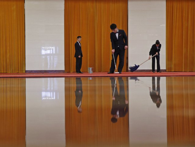 Workers clean carpets before a welcoming ceremony for Austrian President Heinz Fischer at the Great Hall of the People in Beijing, March 27, 2015. (Photo by Kim Kyung-Hoon/Reuters)