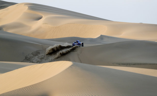 In this January 8, 2019 photo, driver Carlos Sainz and co-driver Lucas Cruz, both from Spain, race their Mini across the dunes during the second stage of the Dakar Rally between Pisco and San Juan de Marcona, Peru. (Photo by Ricardo Mazalan/AP Photo)