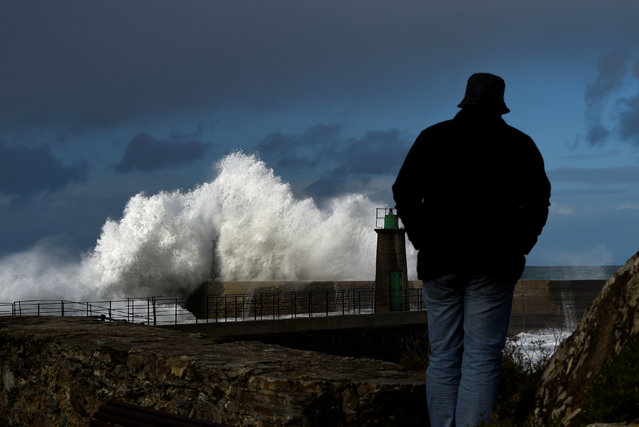 A man looks at waves as they crash against a lighthouse in the northern Spanish village of Viavelez, Spain January 13, 2017. (Photo by Eloy Alonso/Reuters)