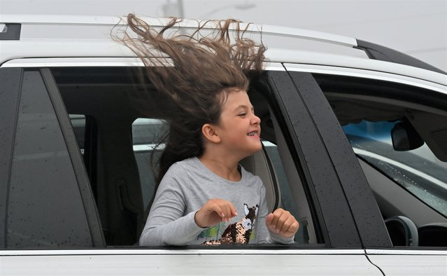 A young girl waits for her family inside their car and the strong winds from Hurricane Henri pull her hair out the window in Maine, USA on August 22, 2021. (Photo by Aimee Dilger/SOPA Images/Rex Features/Shutterstock)