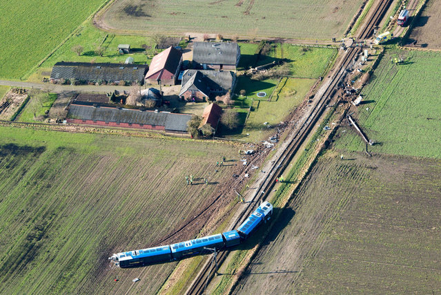 An aerial view of a dereailed passenger train near Dalfsen, eastern Netherlands, 23 February 2016. One person died and six people were injured in a train crash in the north-east Netherlands, officials said. Rail operator Arriva said the deceased was the train driver. Two people were taken to hospital, while four others received only slight injuries, regional security forces said. According to witnesses, at around 9 am (08:00 GMT) a local passenger train collided with a mobile hydraulic platform, the driver of which was attempting to cross the tracks in the town of Dalfsen. (Photo by Bram van De Biezen/EPA)