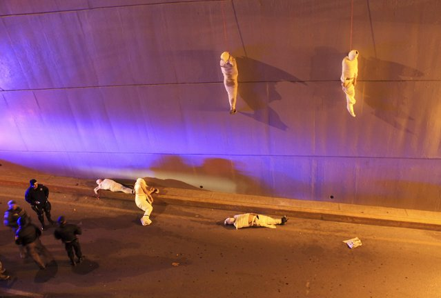 The wrapped bodies of two dead people hang from an overpass as three more dead bodies lie on the ground in Saltillo, Mexico, on March 8, 2013. Three of the five male bodies were hanging from the overpass while two others were lying on the ground when they were found early Friday, according to local media. (Photo by Reuters/Stringer)