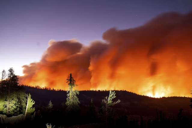 Seen in a long camera exposure, the Caldor Fire burns on Sunday, August 29, 2021, in Eldorado National Forest, Calif. (Photo by Noah Berger/AP Photo)