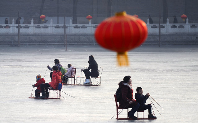 Chinese people use sleds on the frozen lake in Beijing on January 2, 2014. Beijing's lakes attracts scores of tourists and locals who use its frozen surface for skating and ice swimming. (Photo by Wang Zhao/AFP Photo)