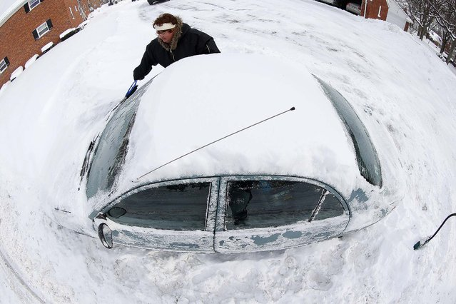 Marguerite Johnston uncovers her car in Grosse Pointe on Monday. Michigan residents are preparing for diving temperatures as they dig out from as much as 15 inches of snow. (Photo by Paul Sancya/Associated Press)