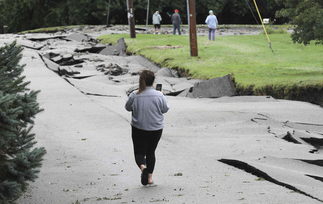 A woman takes video of the severely damaged roadway, Thursday, Sepember 2, 2021, along Fairview Lane, in Portsmouth, R.I., after the remnants of Hurricane Ida passed through the area. (Photo by Scott Barrett/The Newport Daily News/USA Today Network via AP Photo)
