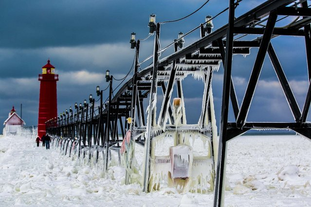 Frozen water clings to the Grand Haven South Pier in Grand Haven, Mich., on January 9, 2014. Cold weather lingered Thursday in the state as many students returned to school for the first time this year. (Photo by Natalie Kolb/The Muskegon Chronicle)