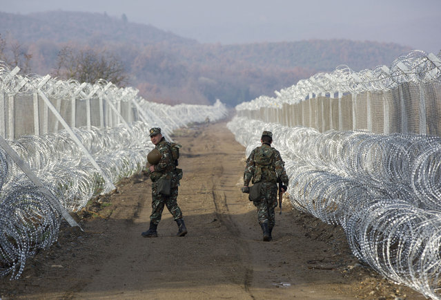 Macedonian soldiers patrol between two lines of protective fence reinforced with barbed wire along the border line between Macedonia and Greece, near southern Macedonia's town of Gevgelija, Tuesday, March 1, 2016. (Photo by Visar Kryeziu/AP Photo)
