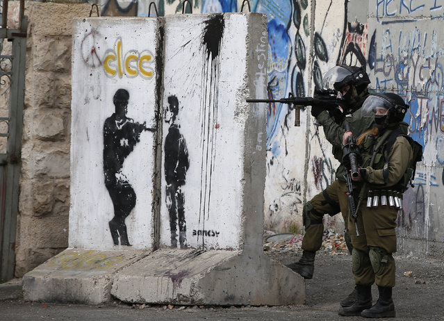 Israeli security force hold a position during clashes with Palestinian stone throwers  following a demonstration demanding that Israeli authorities return the bodies of Palestinians killed during attacks on Israel, in the West Bank town of Bethlehem on January 26, 2017. (Photo by Ahmad Gharabli/AFP Photo)