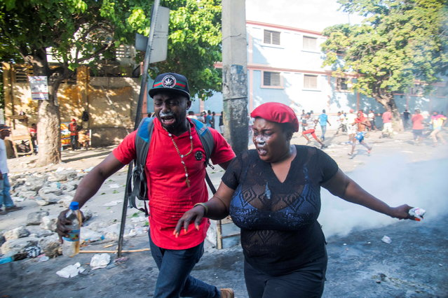 People look for shelter during a protest in Port-au-Prince, Haiti, 09 February 2019. Tension remains high in Haiti after the massive protest held on 07 February against the country's president, Jovenel Moise, and mobilizations called by the opposition continue despite the call for calm and dialogue by the president. (Photo by Jean Marc Herve Abelard/EPA/EFE)