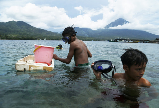 A boy holds his mask as he prepares to catch fish at the beach of Maitara island in Tidore, North Maluku province, Indonesia, March 11, 2016. (Photo by Reuters/Beawiharta)