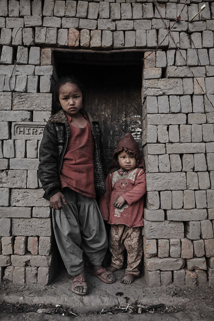 A young girl and her sister lean out of a makeshift doorway during a lengthy shift in Kathmandu Valley, Nepal, 22 February 2015. (Photo by Jan Moeller Hansen/Barcroft Images)