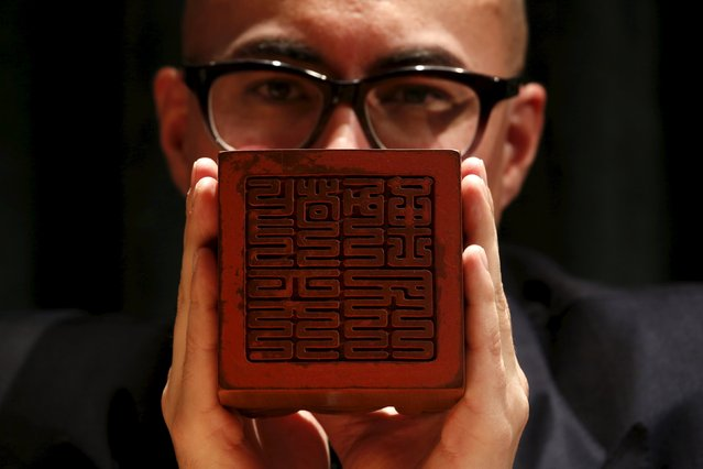 """A seal bearing the inscription """"Revere Heaven and Serve thy People"""", carved for the Kangxi Emperor, is displayed by Sotheby's Asia Deputy Chairman Nicholas Chow at a preview ahead of its April 6 auction in Hong Kong, China, March 14, 2016. (Photo by Bobby Yip/Reuters)"""