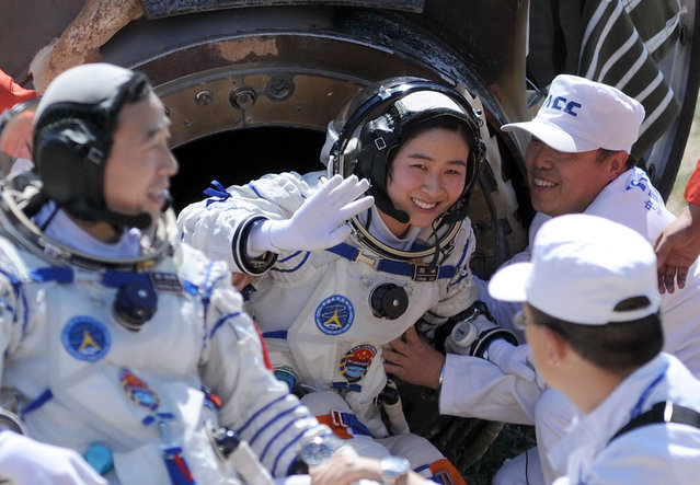 Liu Yang (C), China's first female astronaut, waves next to her comrade Jing Haipeng (L) as she comes out from the re-entry capsule of China's Shenzhou 9 spacecraft in Siziwang Banner, Inner Mongolia Autonomous Region June 29, 2012. The mission put the country's first woman in space and completed a manned docking test critical to its goal of building a space station by 2020. (Photo by Reuters/China Daily)