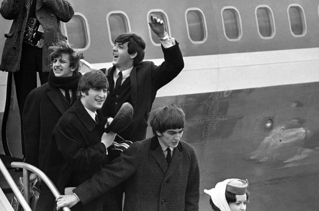 Britain's Beatles make a windswept arrival in New York on February 7, 1964, as they step down from the plane that brought them from London, at Kennedy airport. From left to right, Ringo Starr, John Lennon, Paul McCartney and George Harrison (Photo by AP Photo)