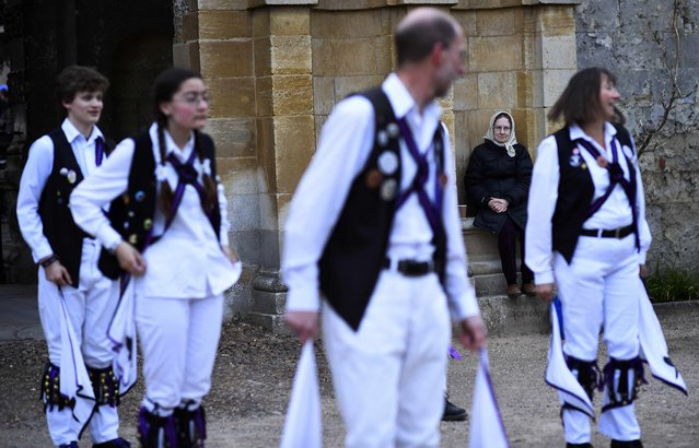 A woman watches as Morris Dancers celebrate in the early hours during traditional May Day celebrations in Oxford, Britain, May 1, 2015. (Photo by Dylan Martinez/Reuters)