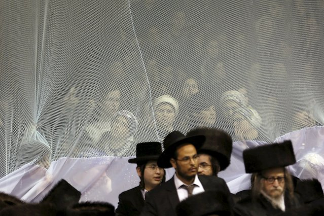 Ultra-Orthodox Jewish men and women attend the wedding ceremony of the grandson of Rabbi Yosef Dov Moshe Halberstam, religious leader of the Sanz Hasidic dynasty, and the granddaughter of the religious leader of Toldos Avraham Yitzchak Hasidic dynasty, in Netanya, Israel, early March 16, 2016. (Photo by Baz Ratner/Reuters)