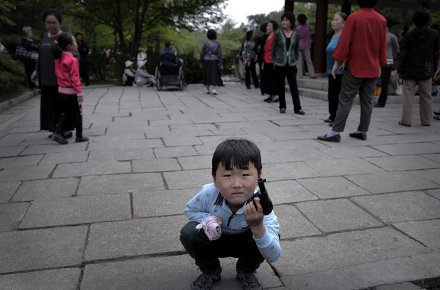 A North Korean boy plays with a toy pistol as elderly people gather around a gazebo, Sunday, May 3, 2015, at the Moranbong, or Moran Hill, in Pyongyang, North Korea. (Photo by Wong Maye-E/AP Photo)