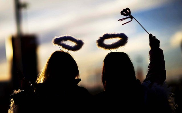Olga Krichevtcova and Ulyana Ukolova wear halos while passing out paper hearts at the Olympic Plaza to celebrate Valentine's Day at the 2014 Winter Olympics in Sochi, on February 14, 2014. (Photo by David Goldman/Associated Press)
