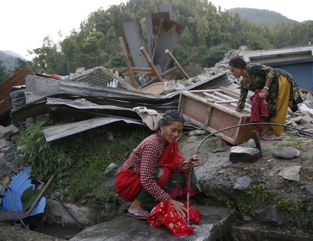 Women wash clothes amongst the ruins of building destroyed by the earthquake near Laharepauwa, Nepal, May 5, 2015. (Photo by Olivia Harris/Reuters)