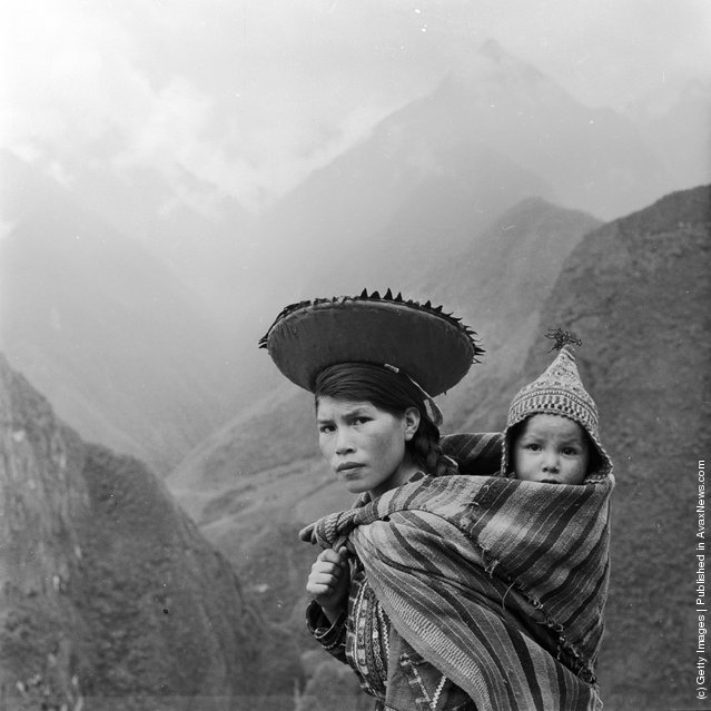 A Peruvian woman treks through the Andes carrying her baby on her back in a fold of her shawl, 1955