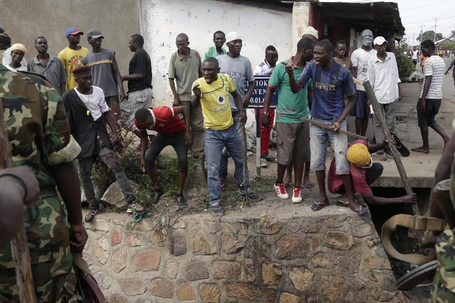 Demonstrators argue with soldiers who want to stop them from killing Jean Claude Niyonzima a suspected member of the ruling party's Imbonerakure youth militia in a sewer in the Cibitoke district of Bujumbura, Burundi, Thursday May 7, 2015. (Photo by Jerome Delay/AP Photo)