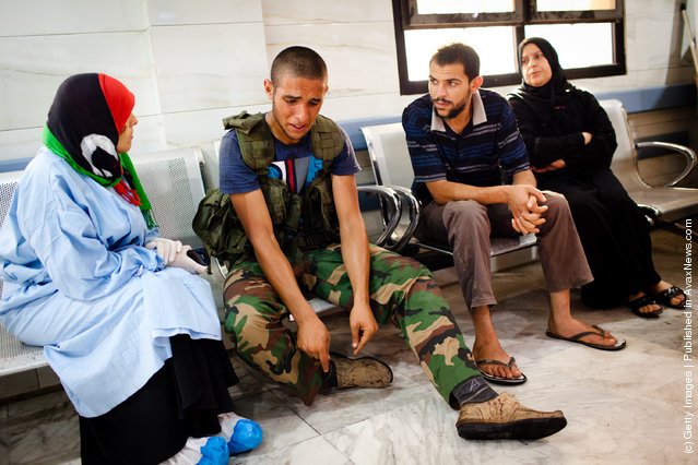 A Libyan Rebel soldier reacts after a fellow fighter