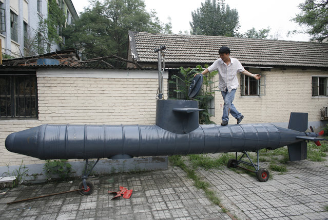 Tao Xiangli stands on his homemade submarine in a courtyard in Beijing July 10, 2008. (Photo by Reinhard Krause/Reuters)