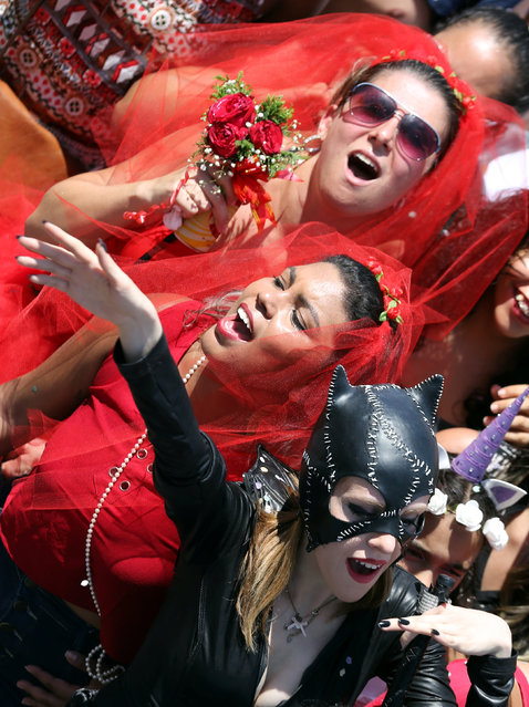 """Revellers dance as they take part in the annual """"Marry me"""" carnival block parade in the main street in Sao Paulo, Brazil February 18, 2017. (Photo by Paulo Whitaker/Reuters)"""
