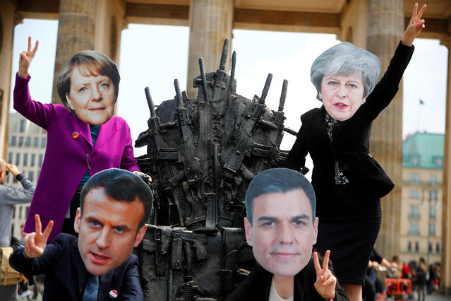 """Activists wearing masks of German Chancellor Angela Merkel, French President Emmanuel Macron, British Prime Minister Theresa May and Spanish Prime Minister Pedro Sanchez pose at an artwork resembling the iron throne from the TV series """"Game of Thrones"""", but made of guns, to protest against exporting arms, in front of the Brandenburg Gate in Berlin, Germany, May 11, 2019. (Photo by Hannibal Hanschke/Reuters)"""