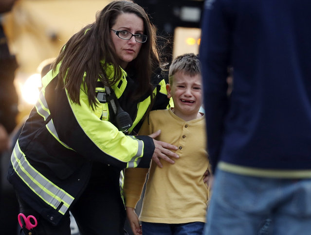 Officials guide students off a bus and into a recreation center where they were reunited with their parents after a shooting at a suburban Denver middle school Tuesday, May 7, 2019, in Highlands Ranch, Colo. (Photo by David Zalubowski/AP Photo)
