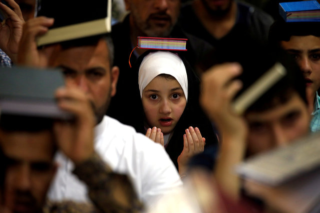 An Iraqi shi'ite muslim girl places a copy of the Koran on her head during the holy month of Ramadan at the Imam Ali Shrine, in the holy city of Najaf, Iraq on May 28, 2019. (Photo by Alaa Al-Marjani/Reuters)