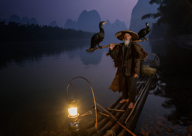 """On the Li River near Xingping in China, Cormorant fishermen work the waterways before dawn amidst the spectacular limestone towers of the Karst landscape.  The birds are trained to fetch fish from the inky depths but not swallow them. The fisherman accepts the fish from the birds who dive back for more. Here, still before dawn, the fisherman and his birds head for home"". (Photo and caption by Neville Jones/2014 Sony World Photography Awards)"