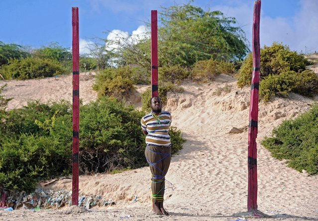 Journalist Hassan Hanafi, convicted of murdering colleagues for the Al-Qaeda-linked Shebab jihadist group, is tied to a wooden post before being executed by firing squad at a police academy square in Mogadishu on April 11, 2016. Hassan Hanafi, was sentenced to death last month after military judges said he had confessed to his role in the killing of five journalists after been arrested in August 2014 in Kenya and extradited to Somalia late that year. (Photo by Mohamed Abdiwahab/AFP Photo)