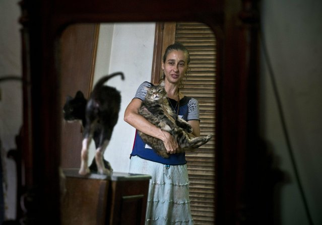 In this Thursday, April. 4, 2019 photo, Grettel Montes de Oca Valdes, a professional dancer and founder of the group Cubans in Defense of Animals poses with cats that were strays in her home in Havana, Cuba. A group of animal-lovers will march a mile down one of Havana's main thoroughfares Sunday waving placards calling for an end to animal cruelty in Cuba. Short, seemingly simple, the march will write a small but significant line in the history of modern Cuba. (Photo by Ramon Espinosa/AP Photo)