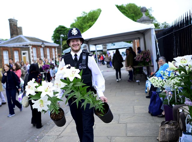 A policeman smiles as he carries lilies away on the final day of the Royal Horticultural Society's Chelsea Flower Show in London, Britain, May 23, 2015. (Photo by Dylan Martinez/Reuters)