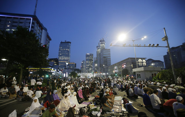 Supporters of Indonesian presidential candidate Prabowo Subianto pray during a rally outside the Elections Supervisory Agency (Bawaslu) building in Jakarta, Indonesia, Tuesday, May 21, 2019. Indonesian President Joko Widodo has been elected for a second term, official results showed, in a victory over a would-be strongman who aligned himself with Islamic hard-liners and vowed Tuesday to challenge the result in the country's highest court. (Photo by Achmad Ibrahim/AP Photo)