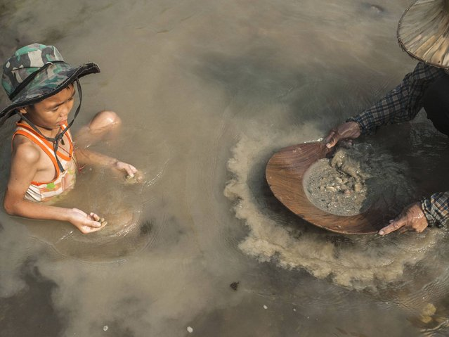 A child plays with the sand as his mother pans for gold in Lampang. Panning for gold takes a lot of patience, but it seems to be worth it as villagers have been supplementing their incomes with it. (Photo by Borja Sanchez-Trillo/Getty Images)