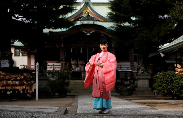 """Shinto priest Tomoe Ichino, 40, poses for a photograph at the Imado Shrine in Tokyo, Japan, February 22, 2017. """"In general, people think being a Shinto priest is a man's profession. If you're a woman, they think you're a shrine maiden, or a supplementary priestess. People don't know women Shinto priests exist, so they think we can't perform rituals. Once, after I finished performing jiichinsai (ground-breaking ceremony), I was asked, 'So, when is the priest coming?'"""", Ichino said. """"When I first began working as a Shinto priest, because I was young and female, some people felt the blessing was different. They thought: 'I would have preferred your grandfather'. At first, I wore my grandfather's light green garment because I thought it's better to look like a man. But after a while I decided to be proud of the fact that I am a female priest and I began wearing a pink robe, like today. I thought I can be more confident if I stop thinking too much (about my gender)"""". (Photo by Toru Hanai/Reuters)"""