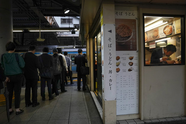 In this Tuesday, May 21, 2019, a man eats his breakfast in a noodle shop located on a platform between two Yamanote Line rails as a group of commuters wait in line to catch a train during morning rush hours at Shinagawa Station in Tokyo. For most Tokyoites, the line means an incredibly punctual and efficient transportation system for commuting. For tourists, it offers a glimpse into the life of ordinary people living in the city. (Photo by Jae C. Hong/AP Photo)