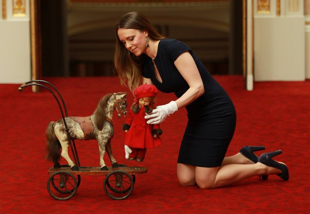 Curator Anna Reynolds with a doll called Pamela and a toy horse on wheels at the launch of the summer exhibition Royal Childhood at Buckingham Palace, London, which celebrates royal childhood with toys and family gifts belonging to the royal children when they were growing up, on April 2, 2014. (Photo by Sean Dempsey/PA Wire)