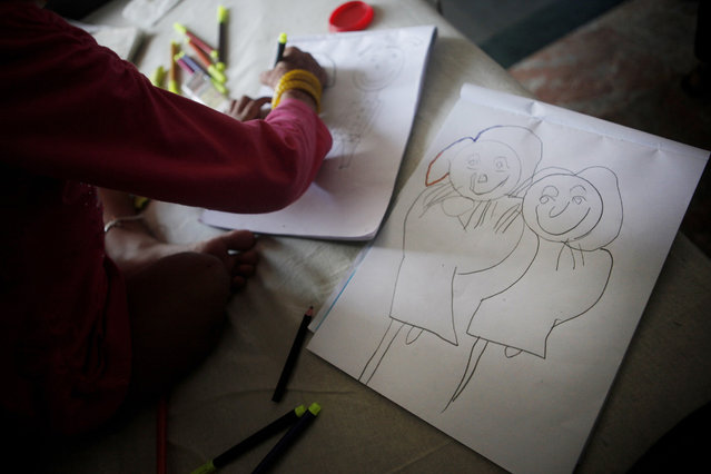 In this July 24, 2015 photo, Nepalese girl Nirmala Pariyar, 8, draws pictures of herself and her friend Khendo Tamang, also 8, at the Bir Trauma Center in Kathmandu, Nepal.  Losing a leg each in the massive Nepal earthquake in 2015, both Nirmala and Khendo were both taken to Bir Hospital and Kathmandu's main trauma ward where they spent the next three months together with surgeries and physical therapy with their new prostheses. During this time the girls' friendship grew and have become inseparable. (Photo by Niranjan Shrestha/AP Photo)